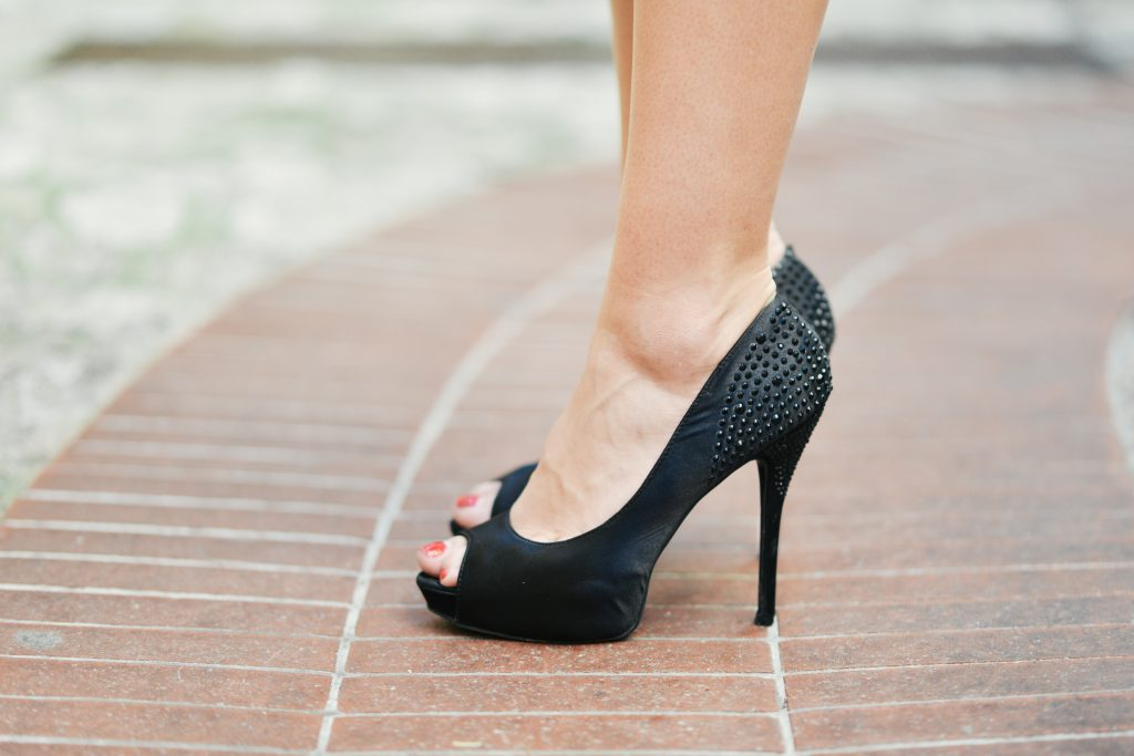 closeup of a woman's legs and feet wearing black shoes
